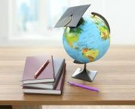 Conceito da educação escolar Placa, livros de texto, globo e pena do almofariz fotografia de stock