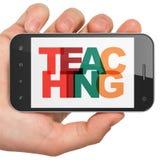 Conceito da educação: Mão que guarda Smartphone com ensino na exposição Foto de Stock Royalty Free