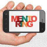 Conceito da educação: Mão que guarda Smartphone com tutoria na exposição Fotografia de Stock