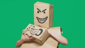 Conceito da emoção, gestos um homem com um pacote em sua cabeça, com um smiley pintado irritado, manhoso, regozijar-se e afagar vídeos de arquivo