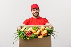 Conceito da entrega - caixa levando considerável do pacote do homem de entrega de Cacasian do alimento e da bebida do mantimento  foto de stock royalty free