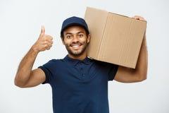 Conceito da entrega - o retrato do homem de entrega afro-americano feliz que guarda um pacote da caixa e que mostra bate acima Is fotografia de stock royalty free