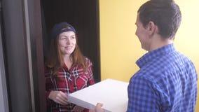 Conceito da entrega da pizza a mulher entrega uma caixa da pizza ao homem vídeo de movimento lento Estilo de vida rápido do conce filme