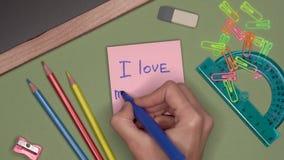 Conceito da escola Escrita da mão da mulher EU AMO MEU PROFESSOR no bloco de notas video estoque