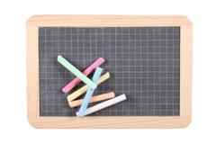 Conceito da escola: feche acima em um quadro-negro da ardósia isolado no fundo branco com gizes e trajeto de grampeamento Imagem de Stock Royalty Free