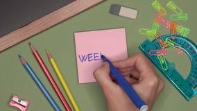 Conceito da escola FIM DE SEMANA da escrita da mão da mulher no bloco de notas video estoque