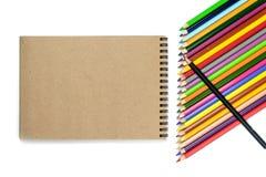 Conceito da escola Lápis coloridos, cadernos no fundo marrom e bege Conceito de projeto - vista superior do caderno e do lápis da foto de stock royalty free