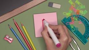 Conceito da escola A mão da mulher que escreve a categoria B, boa marca no bloco de notas video estoque