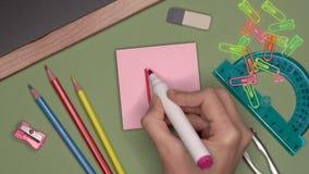 Conceito da escola A mão da mulher que escreve D no bloco de notas vídeos de arquivo