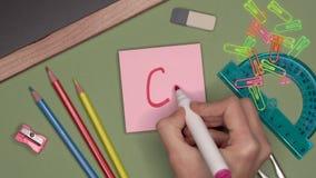 Conceito da escola A mão da mulher que escreve identificar C por meio de marca positiva, satisfatória no bloco de notas filme