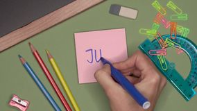 Conceito da escola A mão da mulher que escreve JULHO no bloco de notas video estoque