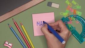Conceito da escola A mão da mulher que escreve MARÇO no bloco de notas video estoque