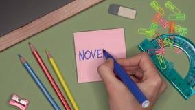 Conceito da escola A mão da mulher que escreve NOVEMBRO no bloco de notas video estoque