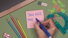 Conceito da escola A mão da mulher que escreve O É o MELHOR PROFESSOR no bloco de notas vídeos de arquivo