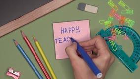 Conceito da escola A mão da mulher que escreve a PROFESSORES FELIZES O DIA no bloco de notas filme