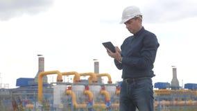Conceito da estação da produção do gás dos trabalhos de equipe Projetando a posição do homem com o capacete de segurança branco d filme