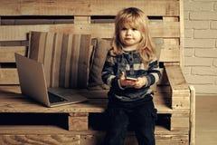 Conceito da felicidade das crianças da infância da criança Caçoe no computador com telefone celular, sms e 4G Fotografia de Stock Royalty Free