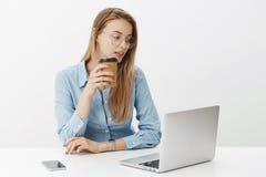 Conceito da finança, do negócio e do trabalho Mulher de negócios fêmea atrativa com cabelo justo nos vidros que bebe o café, trab foto de stock royalty free