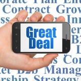 Conceito da finança: Entregue guardar Smartphone com grande negócio na exposição Imagem de Stock