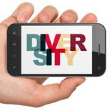 Conceito da finança: Mão que guarda Smartphone com diversidade na exposição Imagem de Stock