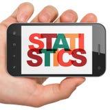 Conceito da finança: Mão que guarda Smartphone com estatísticas na exposição Fotos de Stock