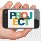 Conceito da finança: Mão que guarda Smartphone com projeto na exposição Imagens de Stock