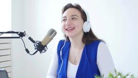 Conceito da flu?ncia e da transmiss?o Fones de ouvido vestindo da jovem mulher e fala na estação de rádio em linha vídeos de arquivo