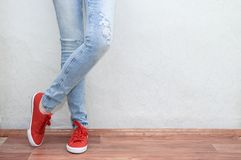 Conceito da forma da mulher Pés fêmeas nas calças de brim e nas sapatilhas imagem de stock