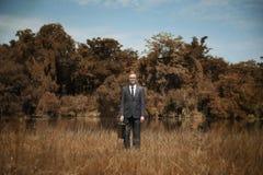 Conceito da grama de Standing Field Brown do homem de negócios imagens de stock