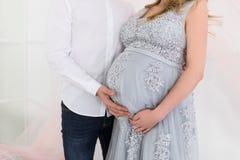 Conceito da gravidez - acople o aperto da barriga grávida Mãos dos membros da família que guardam uma barriga da mulher gravida imagens de stock