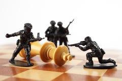 Conceito da guerra Rei da xadrez da matança dos soldados de brinquedo Morte do rei imagem de stock royalty free