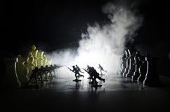 Conceito da guerra Silhuetas dos soldados no tabuleiro de xadrez Conceito da guerra Silhuetas militares que lutam a cena no fundo Foto de Stock