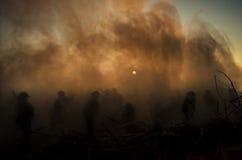 Conceito da guerra Silhuetas militares e tanques que lutam a cena no fundo do céu da névoa da guerra, silhuetas dos soldados da g Foto de Stock