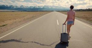 Conceito da imigração downshifting Mulher sozinha com caminhada da mala de viagem na estrada vazia à natureza selvagem filme