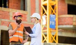 Conceito da indústria da construção civil Discuta o projeto do progresso Coordenador da mulher e construtor brutal farpado para d fotografia de stock