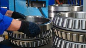 Conceito da ind?stria Rolamento carregando a montagem Unidade para a engenharia mecânica na planta A mão do trabalhador põe um an video estoque
