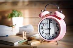 Conceito da instrução Grupo de artigos de papelaria com o despertador na tabela de madeira Foto de Stock Royalty Free