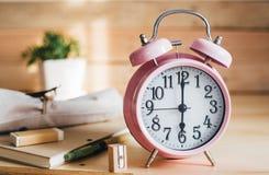 Conceito da instrução Grupo de artigos de papelaria com o despertador na tabela de madeira Fotos de Stock