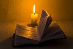 Conceito da instrução Ideia do close-up da vela ardente velha com o livro velho gasto no fundo da tabela Foco na vela imagem de stock