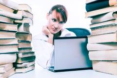 Conceito da instrução Jovem mulher bonita com a pilha de livros com seu portátil no fundo branco fotografia de stock