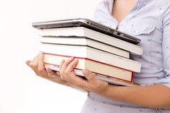Conceito da instrução Mulher que guarda a pilha dos livros e do portátil Fotografia de Stock Royalty Free