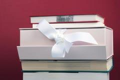 Conceito da instrução O conhecimento está o melhor presente - pilha dos livros no fundo vermelho fotografia de stock