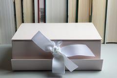 Conceito da instrução Presente no fundo com fileira dos livros fotografia de stock