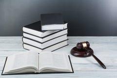 Conceito da lei - livro de lei aberto com um martelo de madeira dos juizes na tabela em uma sala do tribunal ou em um escritório  Fotografia de Stock