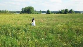 Conceito da liberdade Silhueta do homem de negócio Cowering Menina em um vestido que anda no campo video estoque