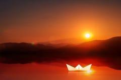 Conceito da liderança Navigação de papel do barco na água com tempo do por do sol Foto de Stock