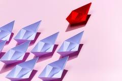 Conceito da liderança Navio de papel vermelho que conduz entre o branco fotos de stock royalty free