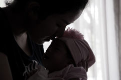 Conceito da ligação do dia da mãe com cuidados recém-nascidos do bebê A mãe é de jogo e de fala com o bebê recém-nascido ao lado  Imagens de Stock