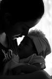 Conceito da ligação do dia da mãe com cuidados recém-nascidos do bebê A mãe é de jogo e de fala com o bebê recém-nascido ao lado  Fotos de Stock