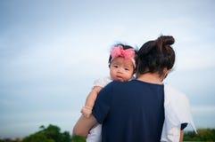 Conceito da ligação do dia da mãe com cuidados recém-nascidos do bebê A mãe está guardando o bebê recém-nascido com a faixa do ro Imagens de Stock Royalty Free